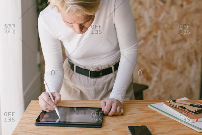 Stylish blond businesswoman bending over table and working on tablet with stylus in light wooden office