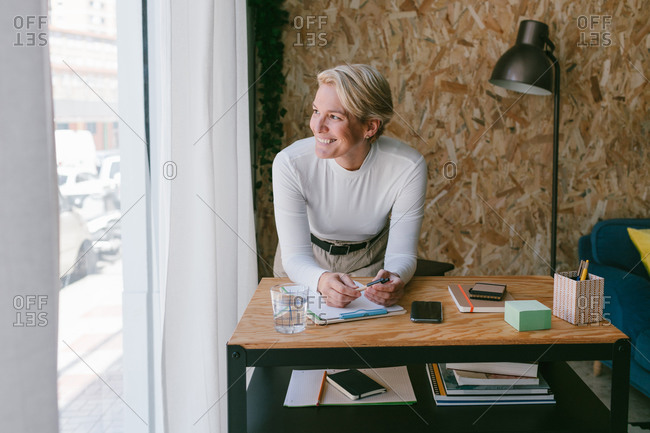 Focused adult businesswoman looking away while taking notes of plan on clipboard bending on wooden table in light office
