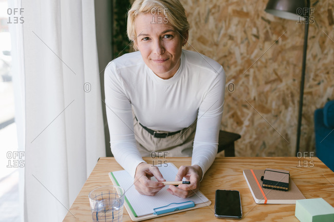 Focused adult businesswoman looking at camera while taking notes of plan on clipboard bending on wooden table in light office