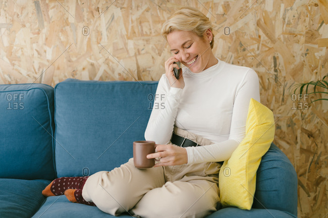 Blonde businesswoman with short hair without shoes chilling on cozy sofa in office enjoying cup of coffee and surfing mobile phone