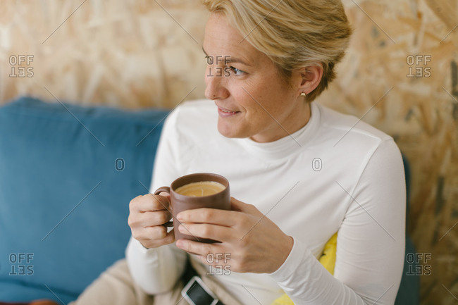 Calm adult businesswoman with short blonde hair sitting on cozy sofa in office having mug of coffee and smiling calmly looking away