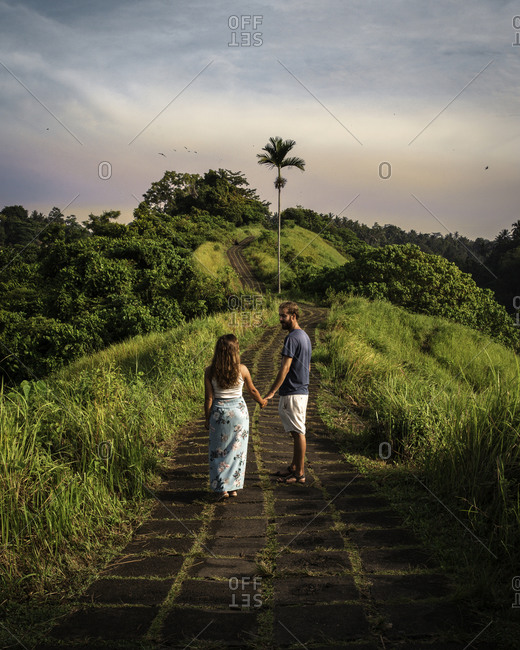 Back view of content young couple in casual wear holding hands while exploring tropical surrounding area during vacation in Indonesia