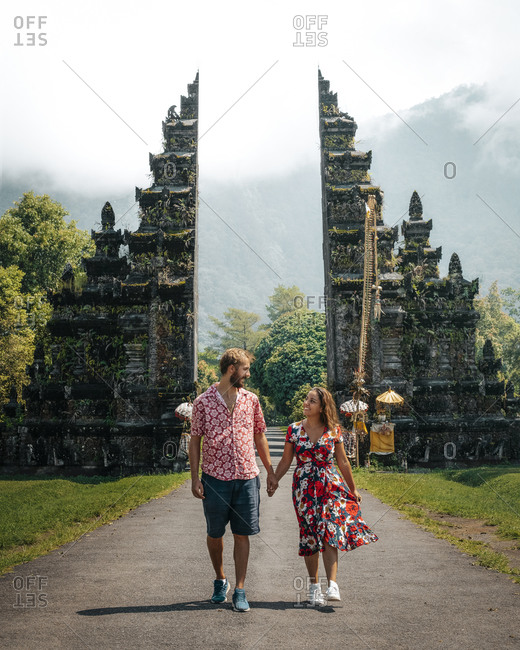 Happy young couple on vacation in light casual wear holding hands smiling and looking at each other while walking on empty path among exotic ancient constructions in Indonesia