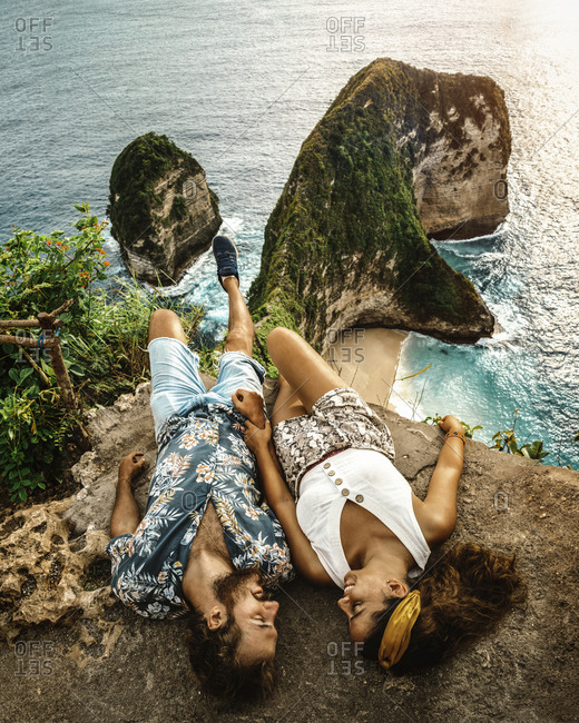 Carefree young couple on vacation in light casual wear lying down on peak of rough cliff and looking at each other with breathtaking landscape on background in Indonesia