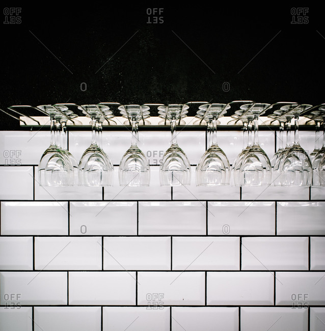 Row of clean polished wineglasses hanging against white tiled wall in vintage bar