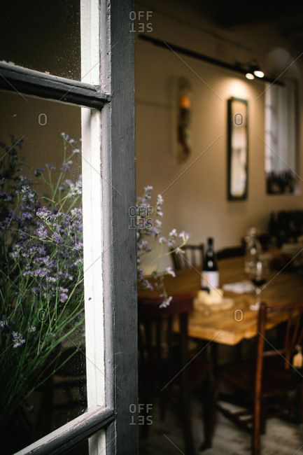 Fragment of interior of rustic restaurant with wooden table served with wine and cheese seen from open window with flowers