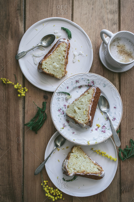 Top view of slices of fresh vegan lemon and coconut cake on plates with spoons and cup of coffee