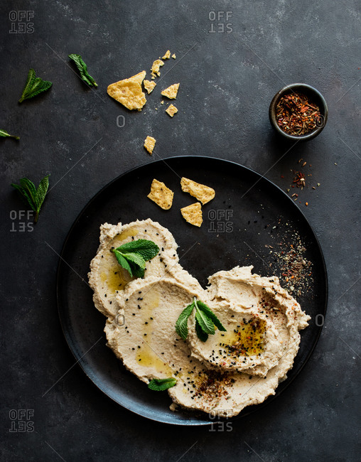 Top view of stylish black plate with delicious fresh eggplant and cauliflower dip stylish decorated with colorful spices and leaves of mint
