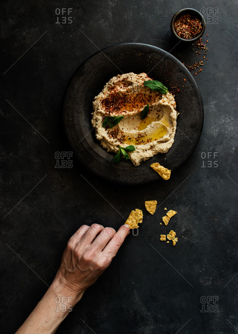 Top view of unrecognizable person hand holding stylish black plate with delicious fresh eggplant and cauliflower dip stylish decorated with colorful spices and leaves of mint