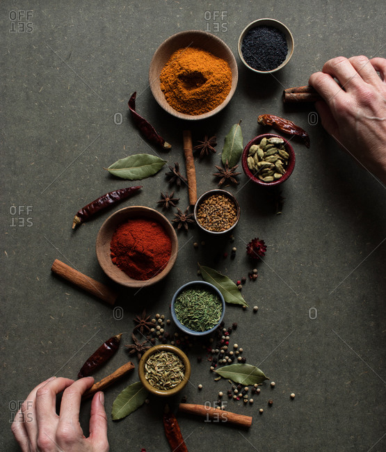 Top view of crop unrecognizable person holding cinnamon sticks near pot with red paprika powder over gray table with set of assorted aromatic spices