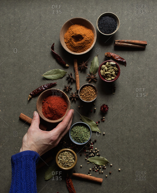 Top view of crop unrecognizable person holding pot with red paprika powder over gray table with set of assorted aromatic spices