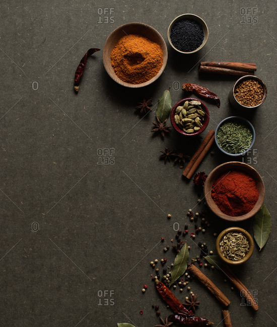 Top view composition with different kinds of natural aromatic spices placed on dark gray background