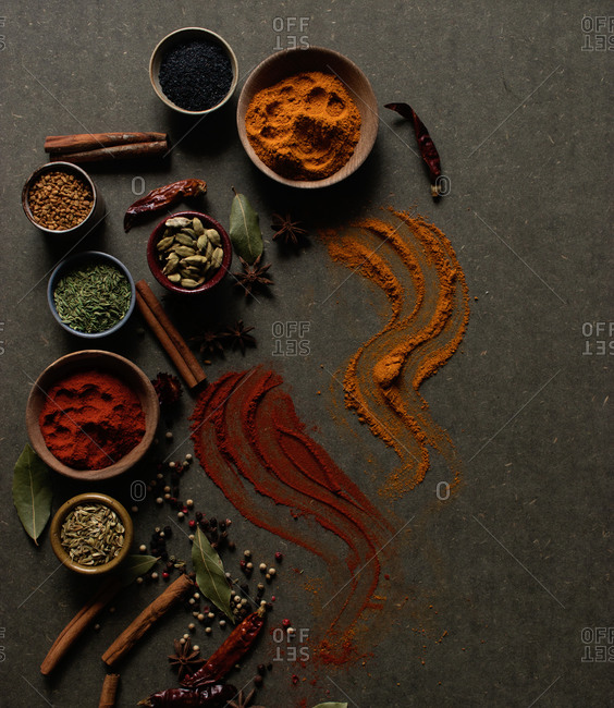 Top view composition with different kinds of natural aromatic spices placed on dark gray background with powder spice spilled on the surface