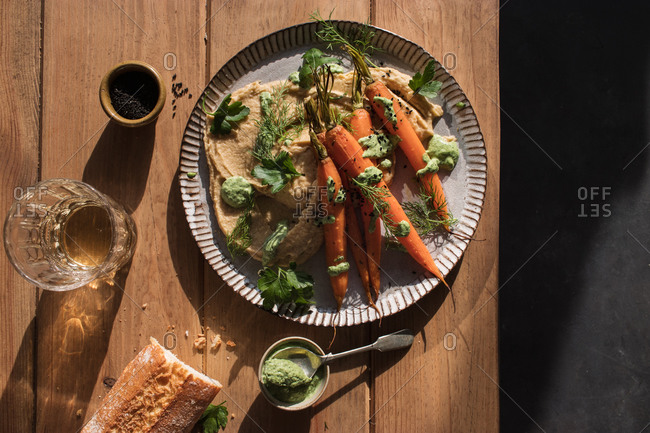 Top view of slices of fresh bread spread with hummus on plate with fresh orange carrots decorated with green sauce on wooden table