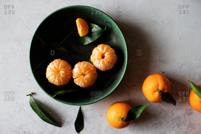 Top view of green ceramic bowl with fresh peeled tangerines placed on white table near unpeeled fruits with green leaves