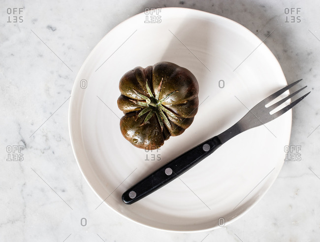 Top view of big unripe green tomatoes on black plate with metal fork and piece of cheese on plate