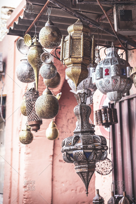 Set of assorted traditional Arabic lanterns hanging on roof outside shabby building
