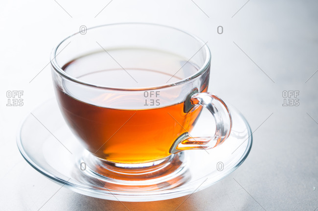 Closeup glass cup of aromatic hot tea placed on saucer on table in cafeteria