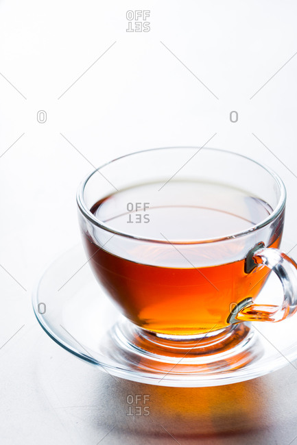 Closeup from above glass cup of aromatic hot tea placed on saucer on table in cafeteria