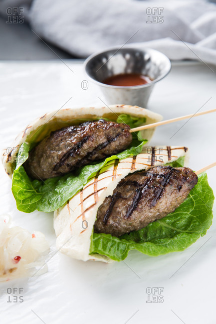 Fresh lettuce leaf and minced meat kebab wrapped in grilled tortilla and placed near cup with spicy sauce on cafe table