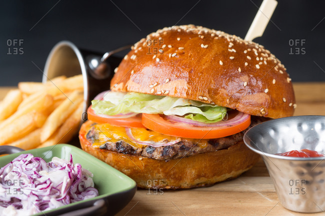 Plate with chopped red cabbage and bowl with sauce placed near delicious burger with lettuce and tomato on patty and bucket of french fries in cafe