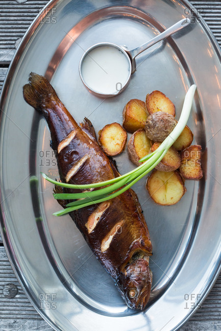 From above delectable fried fish and potatoes with fresh scallion and cream sauce placed on metal plate in restaurant