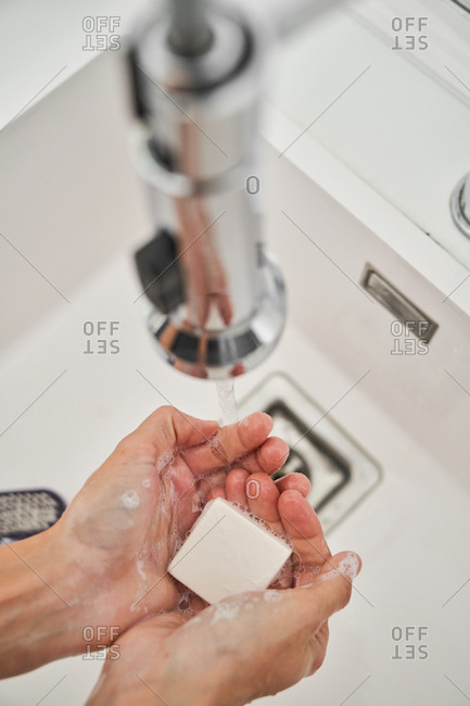 Woman washing her hands on the kitchen sink to avoid possible infection