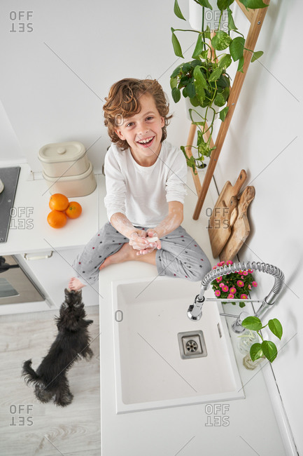 Blond child washing his hands in the kitchen sink to prevent any infection