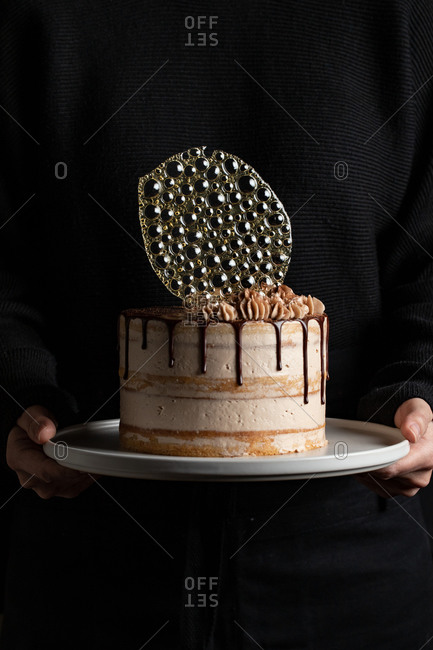 Unrecognizable person holding a festive cake with chocolate filling and frosting and silver isomalt decoration on table with black background