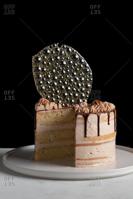 Festive cut cake with chocolate filling and frosting and silver isomalt decoration on table with black background