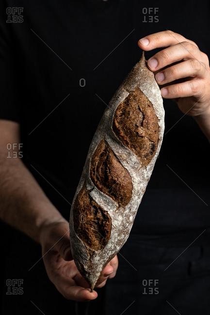 Crop male baker in apron holding fresh healthy artisan bread
