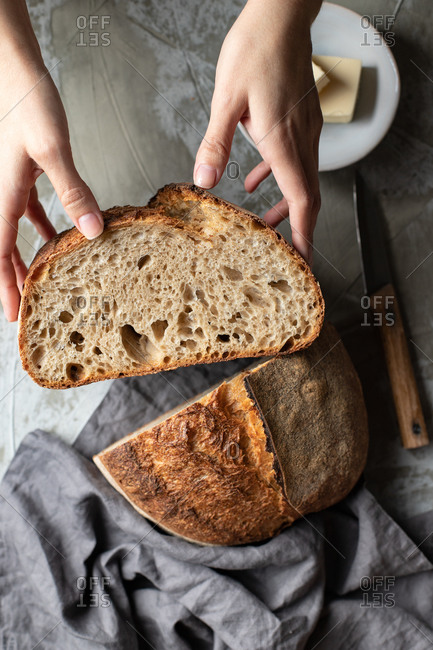 From above of crop female holding cut half of delicious crispy sourdough bread loaf over wooden table with knife and butter