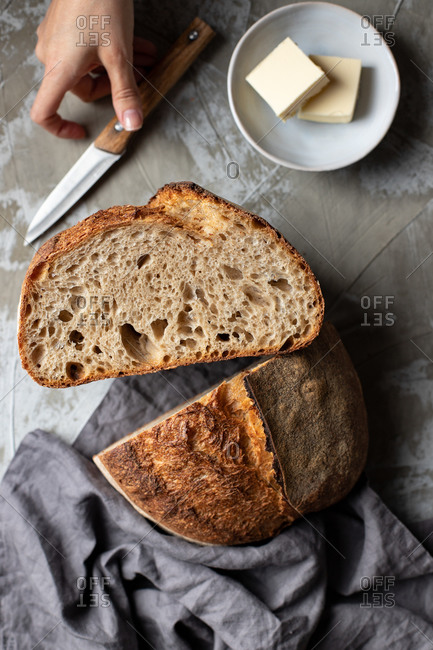 From above of crop female holding knife with cut half of delicious crispy sourdough bread loaf over wooden table with knife and butter