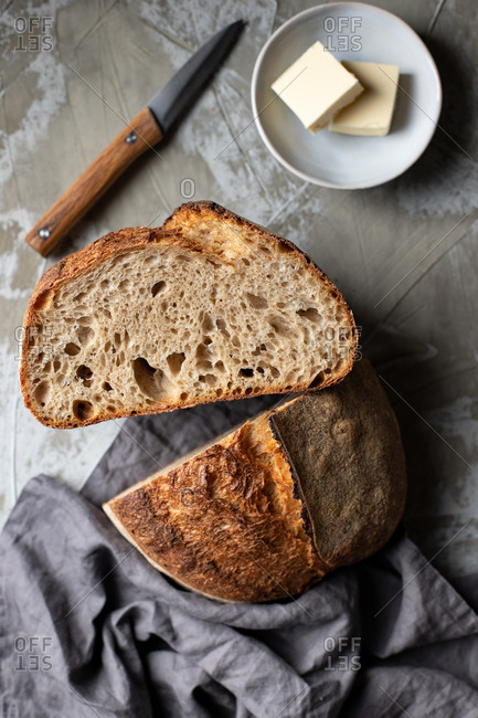 Cut half of delicious crispy sourdough bread loaf over wooden table with knife and butter