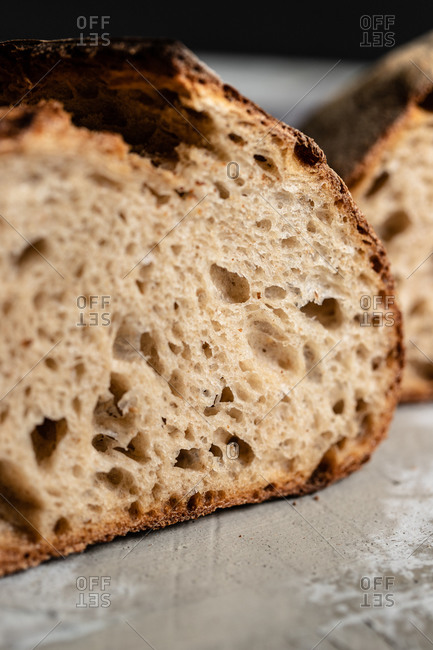Closeup of cut fresh homemade wholegrain bread loaf with crispy crust placed on table