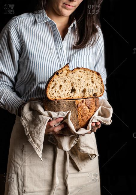 Crop woman baker in apron holding cut in half loaf of fresh healthy artisan bread