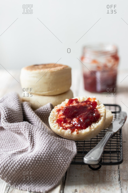 Appetizing freshly baked bun cut in half with homemade strawberry jam placed on metal grid with gray cloth and knife on kitchen table