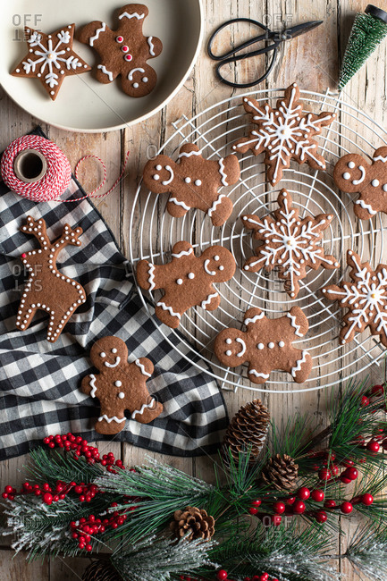 Top view of traditional homemade gingerbread with icing placed on wooden table with decorative tree branch prepared for Christmas celebration