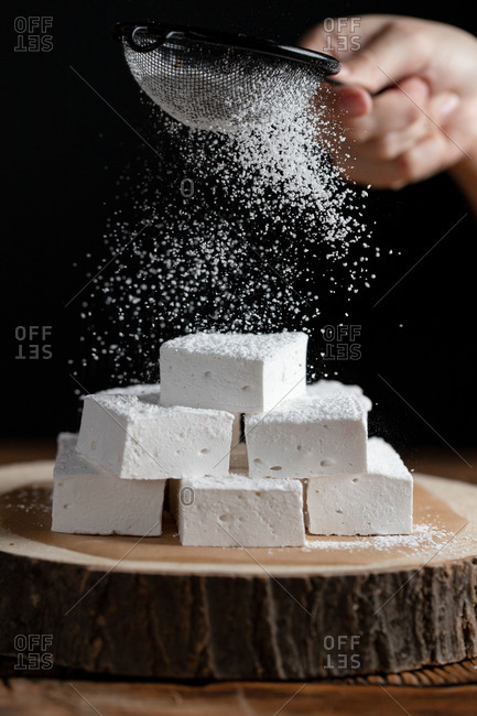 Crop person with sieve sprinkling sugar powder over pieces of marshmallow placed on wooden board against black background