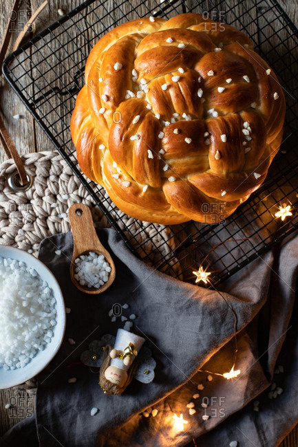 Top view of fresh appetizing braided round bread with sprinkles placed on metal grid on table with Christmas decorative elements