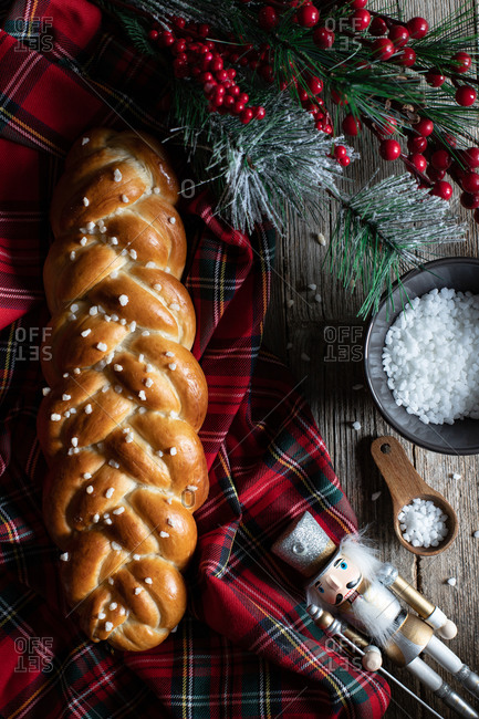 Top view of wooden table with cut traditional braided bread and knife placed on checkered Christmas tablecloth with decorative objects