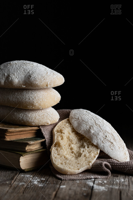Pile of freshly baked tasty homemade bread placed on wooden table next to cut piece against black background