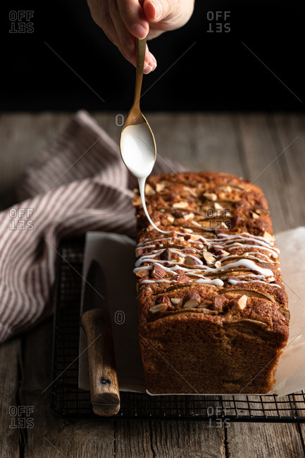 Crop housewife with spoon in hand pouring white sugar icing over homemade banana bread with nuts placed on metal grid on wooden table