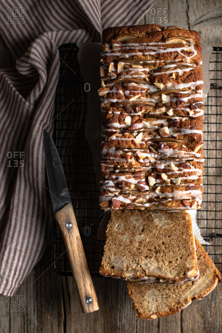 Top view of sliced appetizing homemade banana bread with nuts and sugar icing placed on wooden table with knife and tablecloth