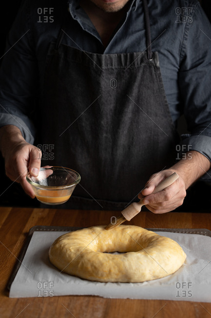Crop male chef in black apron greasing unbaked round bread with egg yolk while standing at wooden table