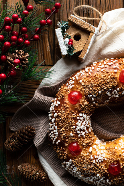 Top view of appetizing cut homemade round bread with hole decorated with sprinkles and cherry placed on wooden table with Christmas decoration