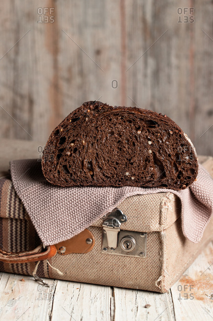 Appetizing healthy dark rye bread loaf with grains cut in half placed on retro fabric suitcase on shabby wooden table