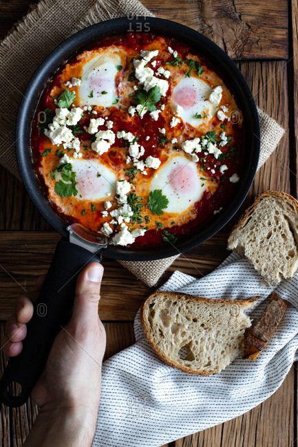 Top view of crop person putting on wooden table frying pan with delicious shakshuka made with fried eggs with vegetables and feta cheese