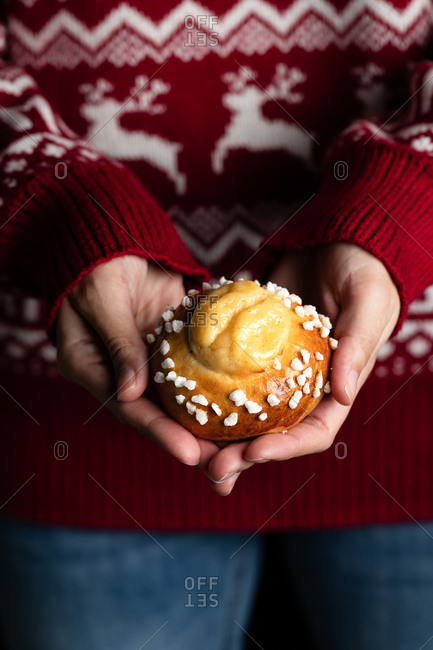 Crop female in red christmas sweater and jeans holding homemade pastry and demonstrating tasty fresh buns with white sprinkles