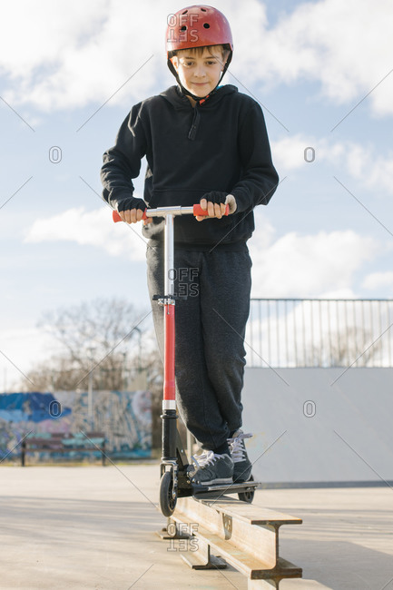 Active teen boy in protective helmet with kick scooter standing on ramp in skate park while preparing for performing trick in sunny spring day